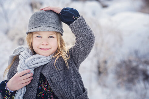 Portrait of cute girl wearing warm clothing standing on field during winter - CAVF60885