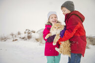 Happy siblings carrying cat while standing on snow during winter - CAVF60888