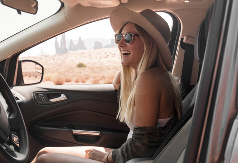 Side view of happy woman wearing hat and sunglasses while traveling in car at Monument Valley Tribal Park - CAVF60918