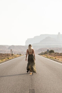 Rear view of woman walking on road against clear sky at Monument Valley Tribal Park during sunny day - CAVF60921