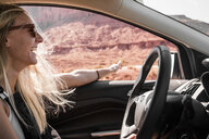 Happy woman wearing sunglasses gesturing while driving car at Monument Valley Tribal Park - CAVF60924