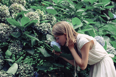 Side view of woman smelling flowers while standing by plants in forest - CAVF60939
