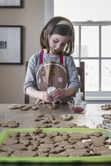 Cute girl putting ingredient on gingerbread man at home - CAVF60966