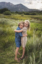 Portrait of happy sisters embracing while standing on grassy field in forest during sunset - CAVF61005