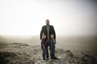 Portrait of father with cute sons standing at beach during foggy weather - CAVF61035