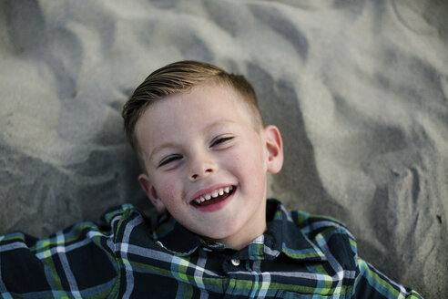 High angle portrait of cute happy boy lying on sand at beach during sunset - CAVF61041