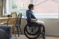 Thoughtful young woman in wheelchair looking out window - CAIF22612