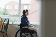 Thoughtful young woman in wheelchair listening to music with headphones at window - CAIF22615