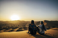 Couple enjoying sunny scenic view of remote, sandy desert, Sahara, Morocco - CAIF22618