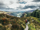 Woman hiking along idyllic mountain path with scenic landscape view, Wicklow NP, Ireland - CAIF22621