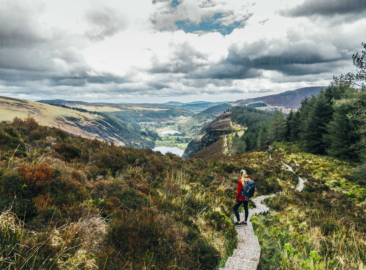 Woman hiking along idyllic mountain path with scenic landscape view, Wicklow NP, Ireland - CAIF22621 - Anna Wiewiora/Westend61