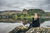 Woman enjoying view of remote, waterfront castle, Scotland - CAIF22627