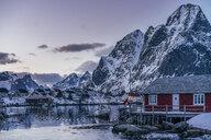Tranquil fishing village below snowy mountains, Reine, Lofoten Islands, Norway - CAIF22630
