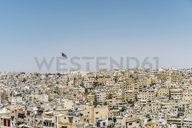 Jordanian flag flying over sunny city buildings, Amman, Jordan - CAIF22633 - Anna Wiewiora/Westend61