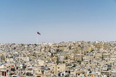 Jordanian flag flying over sunny city buildings, Amman, Jordan - CAIF22633