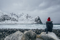 Woman in warm clothing enjoying remote snowy ocean and mountain view, Lofoten Islands, Norway - CAIF22636