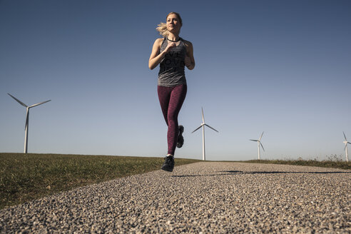 Young woman jogging on field way, wind wheels in the background - SEBF00003