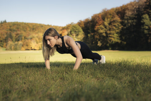 Young woman doing pushups during workout on meadow - SEBF00015
