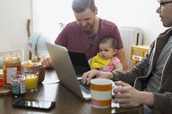 Homosexual couple using technology with baby daughter table - HEROF26046