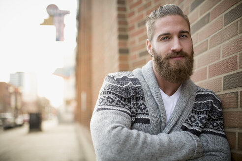 Portrait confident bearded man sweater leaning brick wall - HEROF26100