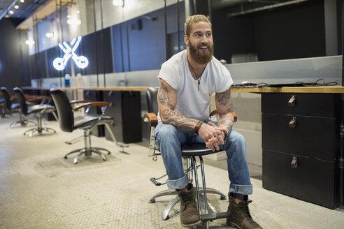 Hipster hairstylist sitting in hair salon - HEROF26109