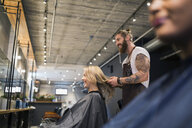 Hipster hairstylist styling customerŒs hair in hair salon - HEROF26112