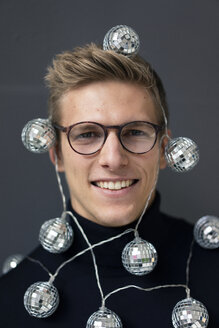 Portrait of smiling young man wearing mirror ball fairy lights - MOEF02074