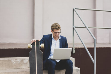 Smiling young businessman with skateboard sitting outdoors on stairs using laptop - MOEF02077