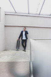 Smiling young businessman with skateboard leaning against a concrete wall talking on cell phone - MOEF02080