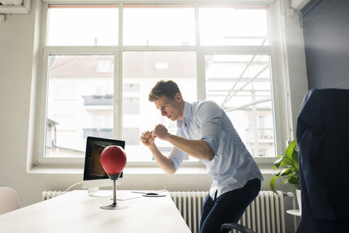 Young businessman at desk in office boxing with punching ball - MOEF02098