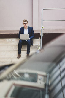 Young businessman with skateboard sitting outdoors on stairs using laptop - MOEF02104