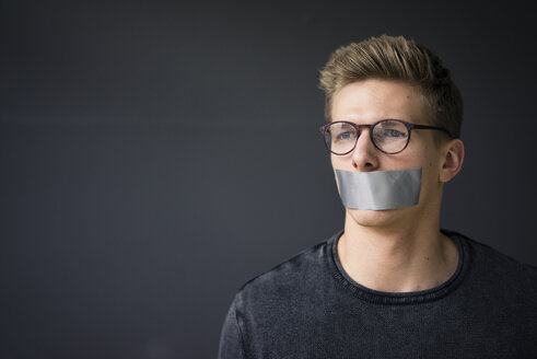 Portrait of young man with taped mouth - MOEF02110