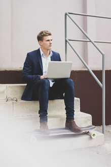 Young businessman with skateboard sitting outdoors on stairs using laptop - MOEF02113