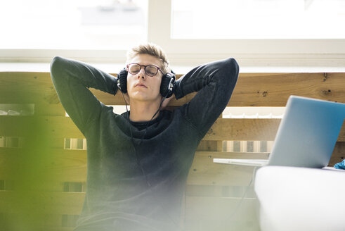 Relaxed young man sitting on the floor listening to music with headphones - MOEF02116