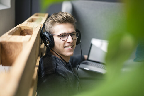 Smiling young man listening to music with headphones - MOEF02122