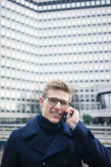 Portrait of smiling young man talking on cell phone in the city - MOEF02131