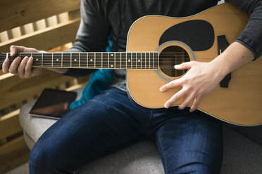 Close-up of man sitting on couch playing guitar - MOEF02140