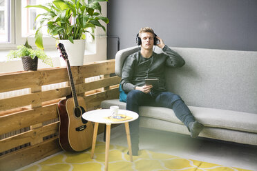 Relaxed young man with tablet and guitar listening to music with headphones - MOEF02143