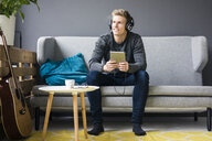 Smiling young man with guitar, tablet and headphones sitting on couch - MOEF02146