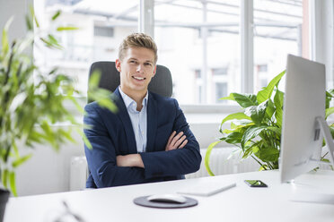 Portrait of confident young businessman sitting at desk in office - MOEF02161