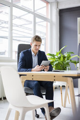 Confident young businessman sitting at desk in office using tablet - MOEF02164