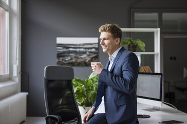 Smiling young businessman sitting on desk in office having a coffee break - MOEF02167