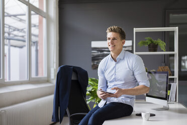Smiling young businessman sitting on desk in office holding tablet - MOEF02170