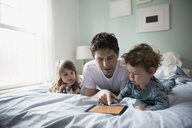 Father and children using digital tablet in bed - HEROF26162