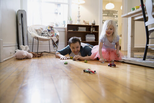 Father and daughter racing toy cars on floor - HEROF26177