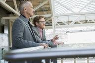 Businessmen talking and looking away in atrium - HEROF26255