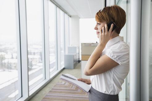 Businesswoman talking on cell phone in corridor - HEROF26258