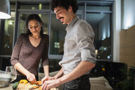 Couple cutting vegetables, cooking dinner in apartment kitchen - CAIF22670