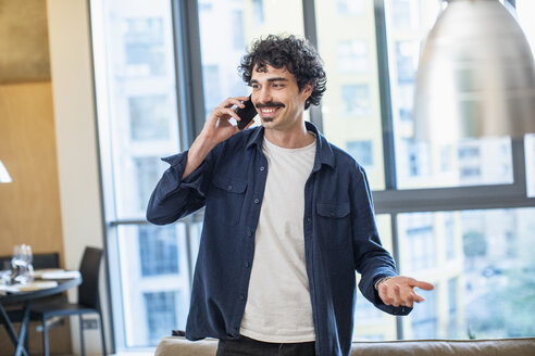 Man talking on smart phone in apartment - CAIF22673