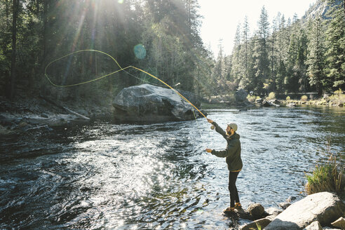 Side view of man Fly-fishing while standing on rock in river at Yosemite National Park - CAVF61062